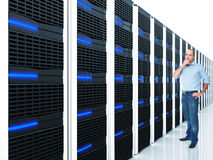 Server at work. Man and datacentre with lots of server selective focus image Stock Photography