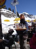 Serveror kommer med skidåkare deras utomhus- lunch Royaltyfri Fotografi