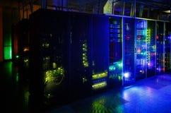 Serverraum in der Dunkelheit, mit hellen farbigen Lichtern Stockbild
