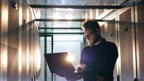 Serverruimte met een mannelijke specialist, IT steuningenieur die aan laptop werken stock video