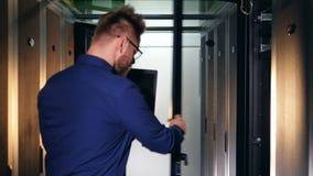 Serverruimte met een IT specialist die de eenheden waarnemen stock video