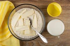 Servet, bloemmengsel met boter voor muffins, lepel in kom, siliconevormen, kop van melk op houten lijst Hoogste mening royalty-vrije stock foto's