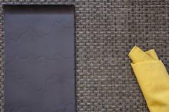 Servetten för den svarta plattan och gulingsnedvrider på bakgrund Royaltyfri Foto
