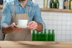 Serveur attentif soigneux mettant une tasse de café sur la table en bois photos stock
