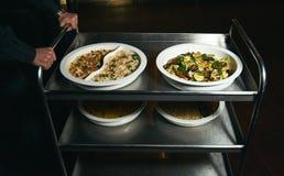 Serveur avec un chariot de portion de nourriture à un restaurant végétarien images libres de droits