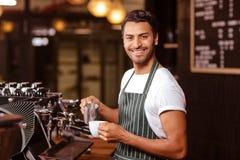 Serveur beau ajoutant le lait au café Photos stock