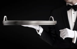 Serveur dans le smoking jugeant un plateau vide d'isolement sur le noir Photo libre de droits