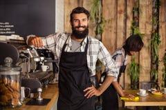 Serveur de sourire se tenant dans la cuisine au café photo libre de droits