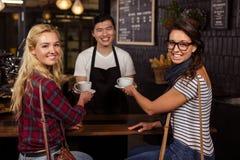Serveur de sourire servant un café aux clients Image libre de droits
