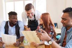 Serveur et amis avec le menu et boissons à la barre Image libre de droits
