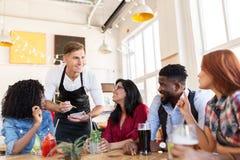 Serveur et amis avec le menu et boissons à la barre Image stock
