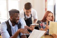 Serveur et amis avec le menu et boissons à la barre Photo libre de droits