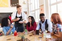 Serveur et amis avec le menu et boissons à la barre Photographie stock