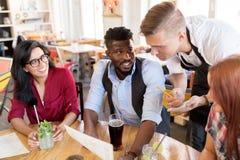 Serveur et amis avec le menu et boissons à la barre Photos stock