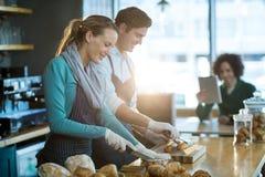 Serveur et serveuse travaillant au compteur dans le café photo stock
