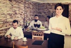 Serveur féminin montrant le restaurant de pays Images libres de droits