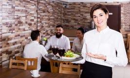 Serveur féminin montrant le restaurant de pays Photographie stock