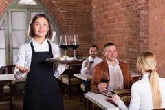 Serveur gai montrant le restaurant de pays Photo stock