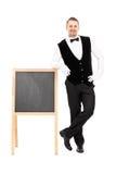 Serveur masculin se tenant à côté d'un tableau noir Photo stock