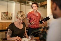 Serveur parlant avec des clients assis à une table de Bistros Photographie stock libre de droits