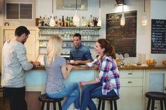 Serveur regardant les clients féminins s'asseyant au compteur en café photographie stock