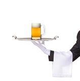 Serveur retenant un plateau argenté avec de la bière là-dessus Images stock