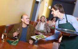 Serveur servant le client masculin supérieur en café Photo stock