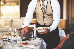 Serveur servant un plat de salade à un invité d'hommes dans un restaurant Images libres de droits