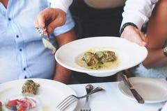 Serveur servant un plat des feuilles de raisin bourré de Grec Images stock