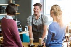Serveur servant une tasse de café au client au compteur Photos libres de droits