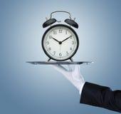 Serveur tenant le plateau argenté avec une horloge Images libres de droits