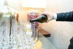 Serveur versant le champagne froid dans des verres sur le fond des lampes images libres de droits