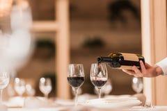 Serveur versant le vin rouge photographie stock