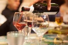 Serveur versant le vin rouge dans des verres Photo stock