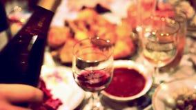 Serveur versant le vin rouge dans un verre à un restaurant banque de vidéos