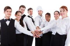 Serveurs et serveuses empilant des mains Photos stock