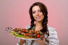 Serveurs portant des plats avec de la viande sur le fond rose Photographie stock libre de droits