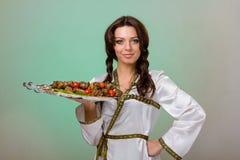 Serveurs portant des plats avec de la viande sur le fond vert Photos stock