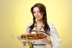 Serveurs portant des plats avec de la viande sur le jaune Images stock