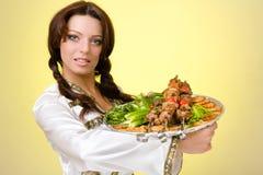 Serveurs portant des plats avec de la viande sur le jaune Photographie stock