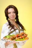 Serveurs portant des plats avec de la viande sur le jaune Photo libre de droits