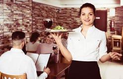 Serveuse apportant la commande pour des invités en café de pays Photos libres de droits