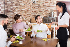 Serveuse de brune et personnes malheureuses dans un café Image stock