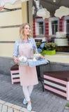 Serveuse de sourire dans le tablier tenant le plateau avec le service à thé en café extérieur Image stock