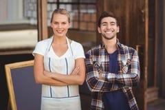 Serveuse de sourire et son collègue avec des bras croisés Photographie stock