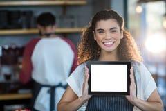 Serveuse de sourire montrant le comprimé numérique au compteur dans le café photos libres de droits