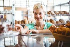 Serveuse de sourire posant le prochain panier du pain Photo stock