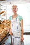 Serveuse de sourire posant le prochain panier du pain Image stock