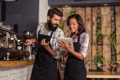 Serveuse employant une tablette et un serveur avec la machine de café photographie stock