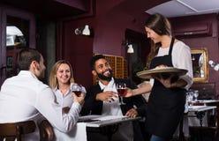 Serveuse et invités de sourire à la table Photographie stock